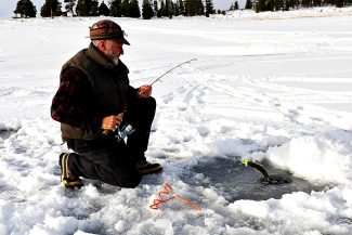 John Grobecker of Edwards lands a fish on Lake Granby duringthe 2013 Three Lakes Ice Fishing Contest.  This year's tournament begins Jan. 23.