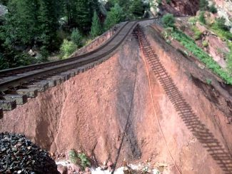 A section of railroad tracks dangles over Lost Bogie Canyon west of Denver, a result of a washout caused by recent torrential rains. Amtrak officials said train travel west from Denver is suspended, and they are not sure when it will be resumed. Photo courtesy Amtrak