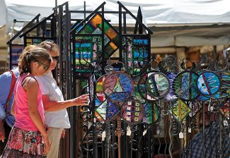 Visitors examine the metal work creations of one of the vendors during a previous Alpine Art Affair in Winter Park.