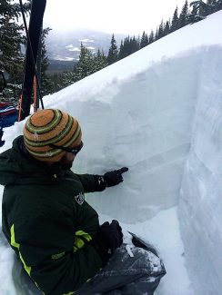 Brian Lazar, a deputy director for the Colorado Avalanche Information Center, points to a weak layer of snow in the snowpack, likely the culprit of the avalanche that claimed the life of George Dirth, 28, of Fraser, on New Year's Eve. The pictured snow pit was dug near the fracture line of the avalanche on New Year's Day while Colorado Avalanche Information Center staff was investigating the accident.