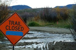 A sign announces the closure of the Fraser River Trail where flooding caused by beavers has overtaken the trail.