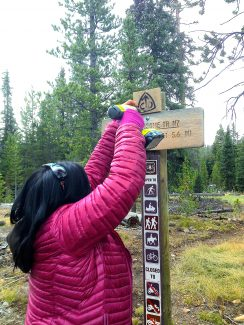 Teresa Martinez of the Continental Divide Trail Coalition replaces trail markers along the trail after the original signs were stolen.