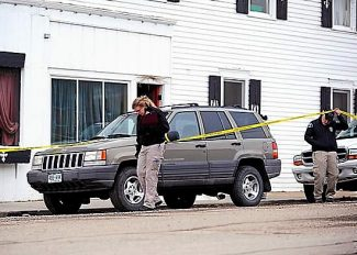 An investigator from the Colorado Bureau of Investigation, left, examines the scene on Tuesday morning of fatal shooting in Hot Sulphur Springs late Monday.