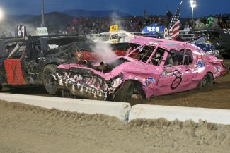Curtis Day, of car No. X, of Evansville, Wyo. smashes the pink car, No. 08, driven by Nancy Healy of Granby, at the Middle Park Fair and Rodeo Demolition Derby on Friday, Aug. 9.