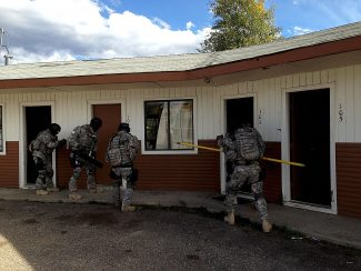 Members of the Emergency Response Team breach a door at the Sunshine Motel during a training on Wednesday, Oct. 2.