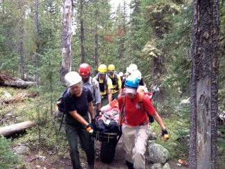 Rescuers transport a man who was suffering from severe altitude sickness to a Flight for Life helicopter on Friday, Aug. 30.