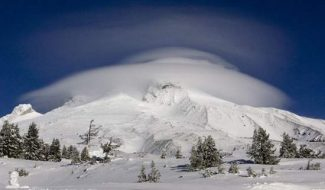 AP PhotoA large lenticular cloud, created by high winds, caps Mount Hood. Rescue crews, politicians, mountaineers and others are debating once again whether to require climbers to carry locator beacons on the mountain.