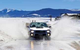 Pete Strohecker drives through a large puddle of water from melting snow on Ten Mile Drive in Granby on Tuesday afternoon.  Mild temperatures are expected again today, which will bring about additional melting.  Byron Hetzler/Sky-Hi News