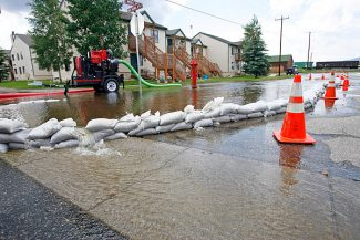 Sandbags and a water pump at the corner of Mill Avenue and Doc Susie Avenue in Fraser help to control water overflowing from St. Louis Creek on Wednesday.  Byron Hetzler/Sky-Hi News