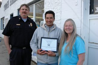 Hot Sulphur Springs citizen John Coffey, center, accepts a Certificate of Appreciation during a Hot Sulphur town board meeting, for his act of heroism on March 24 when he risked his life to rescue children who had fallen into the Colorado River while at play on the river ice. Outgoing board member Kathy Knight, pictured, presented the award, accompanied by Hot Sulphur Springs Fire Chief Brad White, who was involved in the rescue.