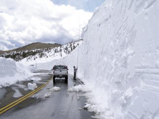 A National Park Service worker measures a 22-foot drift on Trail Ridge Road on May 23.  Courtesy of National Park Service