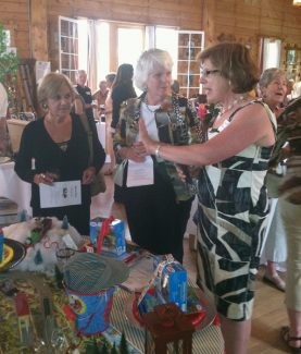 Barbara Davis explains her tabletop with a train theme to potential bidders at Tops of the Rockies fundraiser at the Grand Lake Yacht Club on June 24.