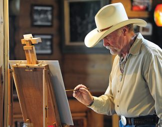 Artist Thomas Holt works on a painting at the Grand Lake Lodge on Wednesday afternoon in Grand Lake.   Byron Hetzler/Sky-Hi News