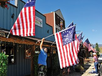 Garey Sutherby helps adorn American flags to the awning of the El Pacifico restaurant on Thursday morning in Grand Lake.  More than 100 flags will decorate town businesses and lampposts as part of Constitution Week festivities in Grand Lake next week.   Byron Hetzler/Sky-Hi News