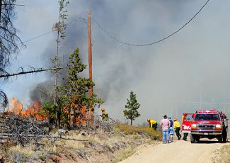 Firefighters battle a small wildland fire on County Road 872 on Wednesday afternoon at the top of Red Dirt Hill.  Granby, East Grand, Grand Lake and Hot Sulphur Springs fire departments responded with equipment and personnel to bring the blaze under control.   Byron Hetzler/Sky-Hi News