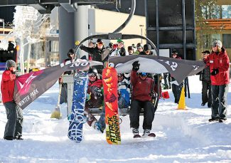 Patrick Curtain, left, Spencer Dailey, center, and Joe Bugos ride the first chair of the season through a ceremonial banner on the Arrow chairlift during opening day festivities on Wednesday morning at Winter Park Resort.   Byron Hetzler/Sky-Hi News