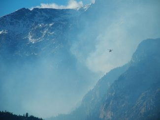 A Type 1 (heavy) Heli-Tanker flies towards Spruce Canyon in Rocky Mountain National Park on Sunday, Nov. 25, to drop water on the Fern Lake Fire. The fire continues to burn and produce smoke and has now burned 1,370 acres and is 40 percent contained. With no winter weather in the immediate forcast and the fire burning in steep and rocky terrain the fire is likley to continue to burn.