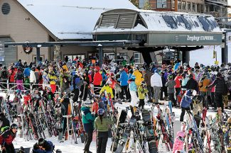 Large crowds of skiers and snowboarders wait at the Zephyr Express chairlift on Saturday morning.   Byron Hetzler/Sky-Hi News