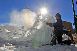 Jess Parrish of Cool Hand Ice works on an ice carving of a dragon on Thursday morning at Winter Park Resort.  The dragon is part of a larger ice castle being constructed for the Winter Park Winter Carnival and Mary Jane's Birthday Bash this weekend.   Byron Hetzler/Sky-Hi News