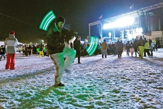 A concert goer dances with glow sticks while Polica performs during the SnowBall music festival on Saturday evening.   Byron Hetzler/Sky-Hi News