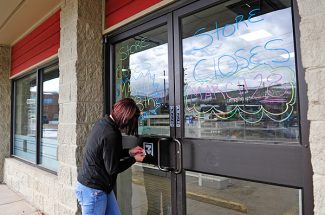 Alexandrya Reynolds scrapes the 7-Eleven logo from the front door of the store in Winter Park on Thursday morning.   Byron Hetzler/Sky-Hi News
