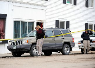 An investigator from the Colorado Bureau of Investigation, left, examines the scene on Tuesday morning of fatal shooting in Hot Sulphur Springs late Monday.  Byron Hetzler/Sky-Hi News