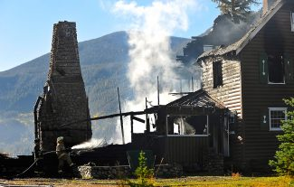 Grand Lake firefighters wet down the smoldering remains of the Buttram home on Tuesday morning, Oct. 1, in Grand Lake.