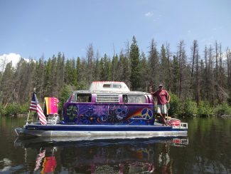 "Clay Williams of Penrose, Colo., floats his Volkswagon-bus-pontoon near the islands of Shadow Mountain Reservoir on Sunday, July 7. Williams said he found the bus minus its engine via online classifieds and decided to make it into a boat cabin. Elaborate paintings embellish the bus, with the words ""Grateful Daze"" artfully painted on the back. Photo by Glenn Chickering"