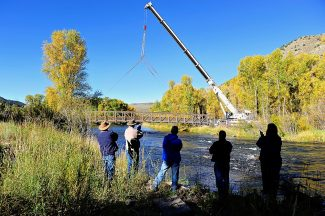 Members of the Hot Sulphur Springs Town Board look on as the new pedestrian bridge is placed over the Colorado River on Thursday morning, Sept. 26.