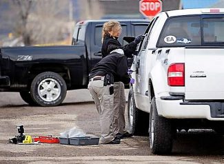 Investigators from the Colorado Bureau of Investigation examine a truck at the scene of a shooting in Hot Sulphur Springs on Monday morning.