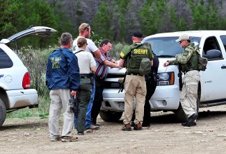 Grand County Sheriff Rod Johnson, center, briefs deputies with plans to search the King Mountain Ranch property for a suspect in a shooting that occurred Wednesday morning, Sept. 11, at the ranch.