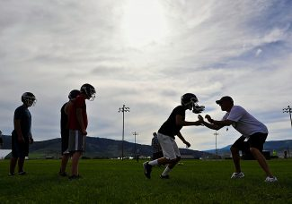 New Middle Park High School head football coach Adam Bright, right, works with players during a preseason camp on Tuesday evening, July 23, in Granby.