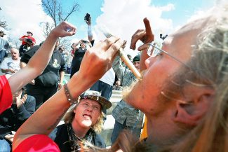 Partygoers listen to music and smoke marijuana on one of several days of the annual 4/20 marijuana festival, in Denver's downtown Civic Center Park, Saturday, April 18. The annual event is the second 4/20 marijuana celebration since retail marijuana stores began selling in January 2014.
