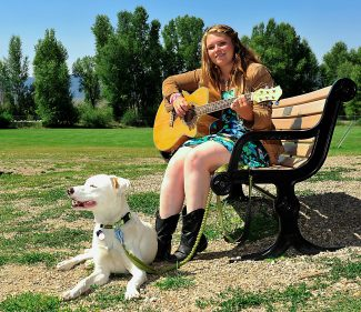 Morgan Hale plays her guitar in Kaibab Park with her dog Spirit on Thursday, Aug. 15, in Granby.