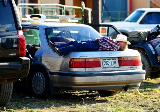 A young cowboy rests on the trunk of a car at the High Country Stampede rodeo on Saturday, Aug. 2, at the John Work Arena in Fraser.