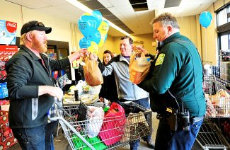 Grand County Sheriff Rod Johnson, center, and Deputy Burke Payne, right, collect food during the Sheriff's Department's annual food drive at City Market on Saturday, Nov. 16, in Granby.  The food drive was to help with the Mountain Family Center's Thanksgiving Basket Project.