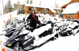 Cody Holt sweeps snow from rental snowmobiles at the Spirit Lake Lodge on Thursday morning, Jan. 30, in Grand Lake.  More snow is forecast through today.