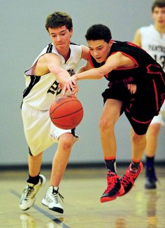 Middle Park's Chris Cox, left, and Denver School of Science & Technology's Jordan Heien battle for a loose ball during Monday's, Feb. 17, game in Granby.  The Panthers lost 84-51.