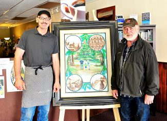 Howard Neville, right, and Simon O'Connor owner of the Mid Town Cafe pose with Neville's original artwork for a poster to commemorate Rocky Mountain National Park's upcoming 100th anniversary on display at the cafe in Granby.  Another of Neville's original paintings for another poster is on display at the Western Riviera in Grand Lake.