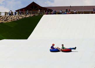 Visitors take a ride down the new summer tubing hill at Snow Mountain Ranch on Wednesday afternoon, July 16. The attraction, which opened for operation on Tuesday, is the first of its kind in Colorado and just the third in the country.