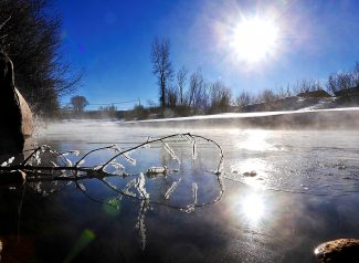 A branch coated with hoar frost is reflected in ice on the Fraser River on Thursday morning, March 13, in Granby.  More mild weather is expected in the coming days, aside from a chance of snow on Saturday.