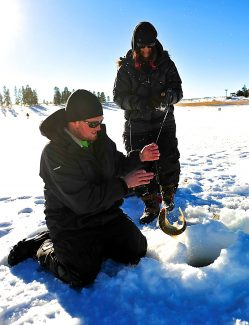 Nick Thompson, left, helps Dee Orozco, both of Colorado Springs, land a fish on Lake Granby during the Three Lakes Fishing Contest on Saturday, Jan. 25.