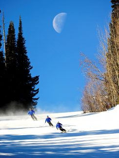Instructors from the Winter Park Ski and Ride School make turns down the Larry Sale trail at Winter Park Resort on Thursday morning, Jan. 23, as the moon sets behind them.