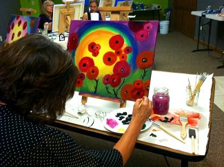 Jody Mimmack works on a painting at Studio 564 in Fraser.