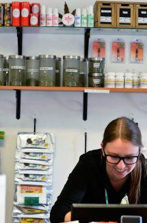 Kaitlyn Welch, 25, from New Castle, helps a customer in May at the Green Dragon Cannabis Company on Devereux Road in Glenwood Springs.