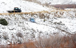 Employees of First Class Auto work to bring a car back up to the roadway along U.S. 40 at the east side of Windy Gap on Thursday morning, Oct. 31.  The vehicle was involved in a rollover accident and came to rest in the Colorado River. The accident took place at a slippery area, where three cars slid in a matter of 10-15 minutes. According to EMS, drivers in all three vehicles were not injured, including the driver of the car pictured here.