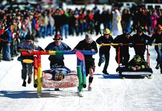 The team from Pancho and Lefty's pulls ahead against the team from the Grand Lake Fire Department during a heat of the bed sled races during last year's Grand Lake Winter Carnival.  This year's winter carnival takes place on Saturday, Feb. 1, with events throughout the day.