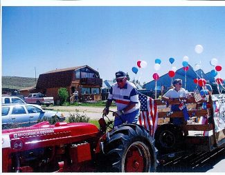 Jerry Woods drives one of his International tractors during a Fourth of July parade in Granby. Woods, a former mayor of Granby and Grand County Commissioner, died Jan. 20 at the age of 86.