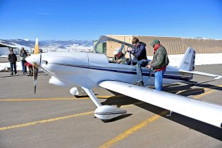 Pilot Rod Kauber, left, and Rudy Perez, right, assist David Gantt as he prepares to a Young Eagles flight with Kauber at the Granby Airport on Friday morning, May 3.  The free flights were offered by the local chapter of the Experimental Aircraft Association to give children the experience of flying.  Byron Hetzler/Sky-Hi News