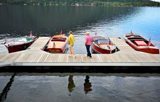 Visitors examine several of the classic boats on display during the Grand Lake Wooden Boat show at the town docks on Saturday morning, July 13, in Grand Lake.